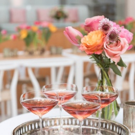 four glasses with rose on silver platter