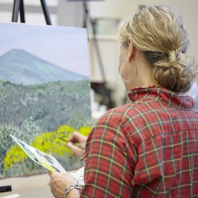 Woman working on a landscape painting
