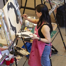 Woman painting portrait at an easel