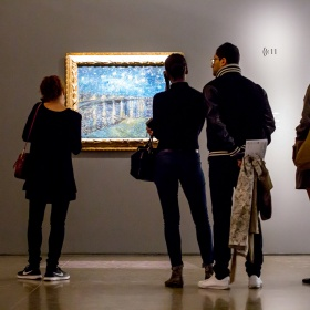 People looking at a painting, and listening to audio guides, in an exhibition