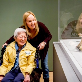 A woman in a wheelchair looking at a sculpture