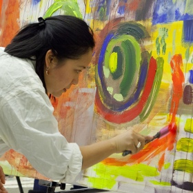 Woman working on large abstract painting