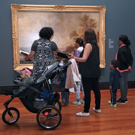 people with child in stroller looking at a painting in gallery