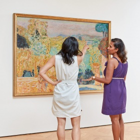Two people looking at art in the gallery