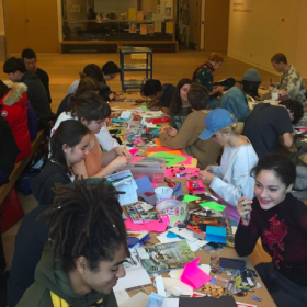 youth at long tables making postcards