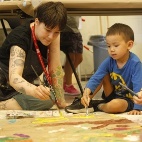 child and caregiver sitting on the floor painting