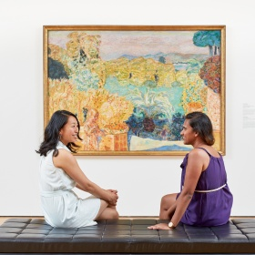 two people sitting in front of a painting