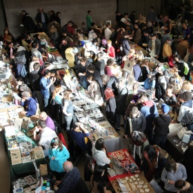 overhead photo of canzine festival with vendors selling printed materials at long tables