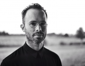 back and white headshot of artist daniel Arsham, wearing round metal framed glasses and black shirt