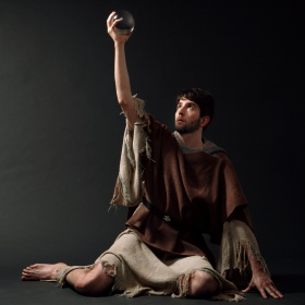 Composer Owen Pallett in rustic tunic holding a crytal orb