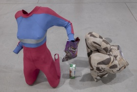installation photo of sculpture featuring woman's leotard, doritos chips bag, beverage tetra pack and patchwork pants.