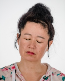 heashot of artist Hito Steyerl with her eyes closed in a floral hoodie