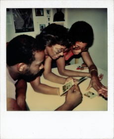 found polaroid image of three family members looing at polariois photos