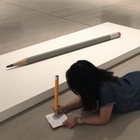 person on floor next to Celmins pencil sculpture, writing with large pencil