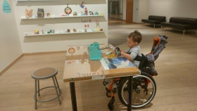 Noah is sitting in his wheelchair at the Mindful Makers exhibit at the AGO.