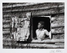 Gelatin silver print of young person looking out log cabin window