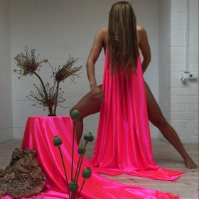 Still of Slow Death performance featuring neon pink satiny fabric