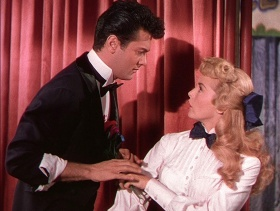 Actors Tony Curtis and Janet Liegh in front of a red velvet curtain, as Harry and Bess Houdini