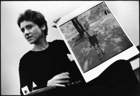 Photographer Diane Arbus in black holding a print of her photo while discussing her work in a presentation