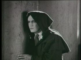Harry Houdini as Heath Haldane in a black hooded cape in a still from the film