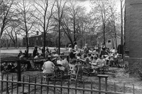 Black and white photo of Arthur Lismer conducting a children's outdoor sketching class in Grange Park