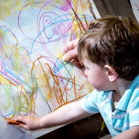child drawing with chalk pastel