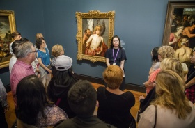 Tour guide stands in front of crowd of visitors. Behind the guide is a painting of an angel.