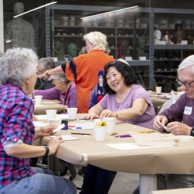 Group of smiling people around a table, covered in brown paper, making art.