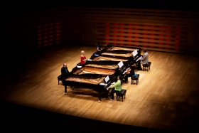 Six people are seated in front of six contiguous pianos.