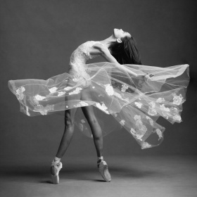 A dancer stands en pointe in a white semi-transparent dress.