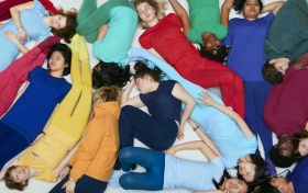 A group of people lay in the ground in monochromatic outfits.