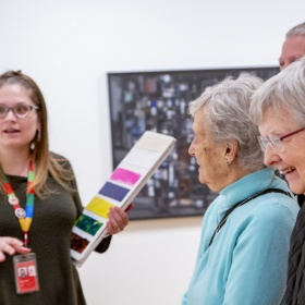 An AGO Art Educator stands to the left holding a board with painted colours. They wear a green shirt and a rainbow lanyard. On the right, there are three elderly individuals smiling. A painting can be seen in the background out of focus.