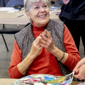 An individual in an orange shirt and grey vest sits at a table in front of an abstract painting. They smile, clasping their hands together. A figure in black, with their back turned to the camera, can be seen in the background with their hand of their hips.