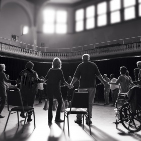 A large room filled with a crowd of dancers holding hands. Chairs and wheelchairs are seen in the foreground. The image is in black and white, becoming more out of focus as you move towards the top of the photo.