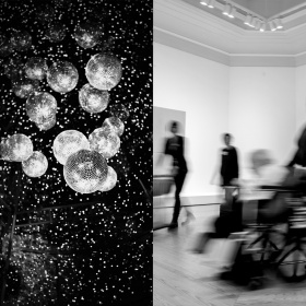 (Left) Disco balls hang from the celling surrounded by sparkling lights. (Right) A individual in a wheel chair and two individual standing upright pass across the frame. They are blurred, out of focus.
