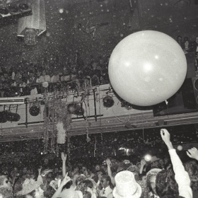 A large room. There is a crowd standing below with a series of onlooker perched upon the second floor mezzanine. A very large white ball can been floating in the center of the frame.