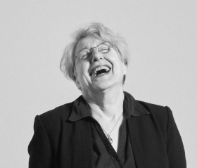 black and white headshot of the artist laughing with her head thrown back