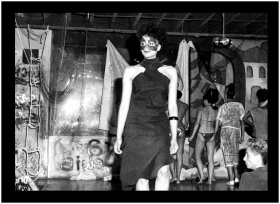 black and white image of a model wearing a dress with shoulder cut-outs and eye maskin a fashion show at Twilight Zone, an afterhours club in Toronto