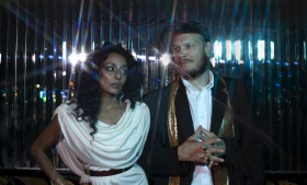 high contrast photo of speakers Arshia Haq in a draped white dress and Jeremy Loudenback in black suite, white shirt and sparkling lamé scarf