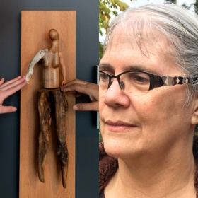 "Image split into two: On the left a photo of two hands outside the frame reaching to touch a sculpture by Persimmon Blackbridge. The piece is titled ""Soft Touch"", and is a handcrafted figure made of wood, bone and plastic to resemble a person constructed from found objects. It is mounted on a wood panel. On the left photograph head shot of figure wearing glasses with white hair"