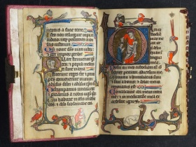 an image of a medieval book showing gothic text will illustrations in red, gold and blue on the edges of the page and text