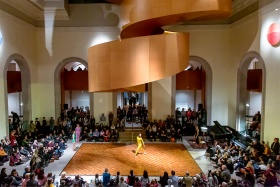AGO's Walker Court full of people, a square dance floor centred under the spiral stairs, featuring a dancer in a yellow unitard