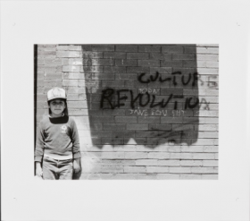"Black and White photograph of a young boy wearing a baseball cap standing against a brick wall with the words ""culture Revolution"" written"
