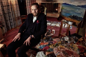 Portrait of artist Ragnar Kjartansson wearing a black suit, sitting in a chair surrounded by oil paint palettes and a painting on an easel