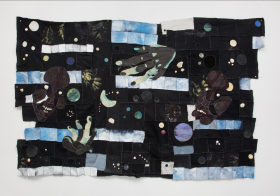 An image of a textile work by Tau Lewis, featuring recycled fabrics and leather, acrylic paint, stones, sea shell in mostly blacks, blues and whites with figures of faces and hands,