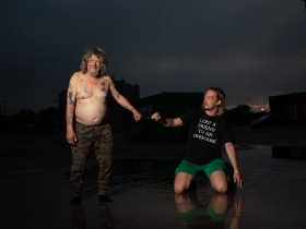 "image of two men, brightly lit against a dark outdoor background. The man on the left wears camo-print pants, on the right a man wears a tshirt that reads ""lost a friend to an overdose"", green shorts and is kneeling. They are reaching out fists to each other."