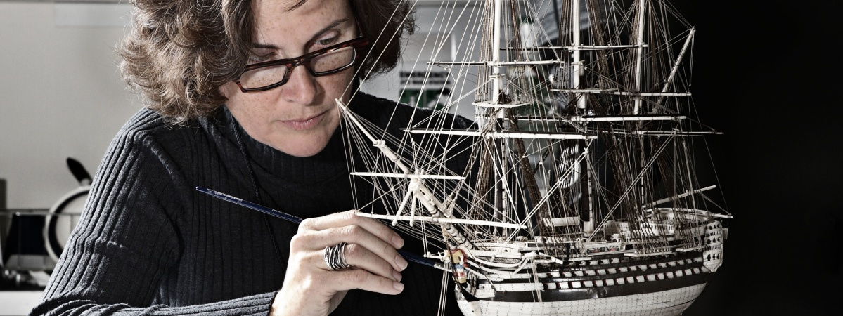 conservator working on ship model