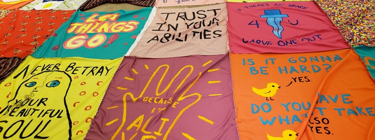 hand painted messages on brightly coloured fabrics and then stitched together to create a large scale quilt