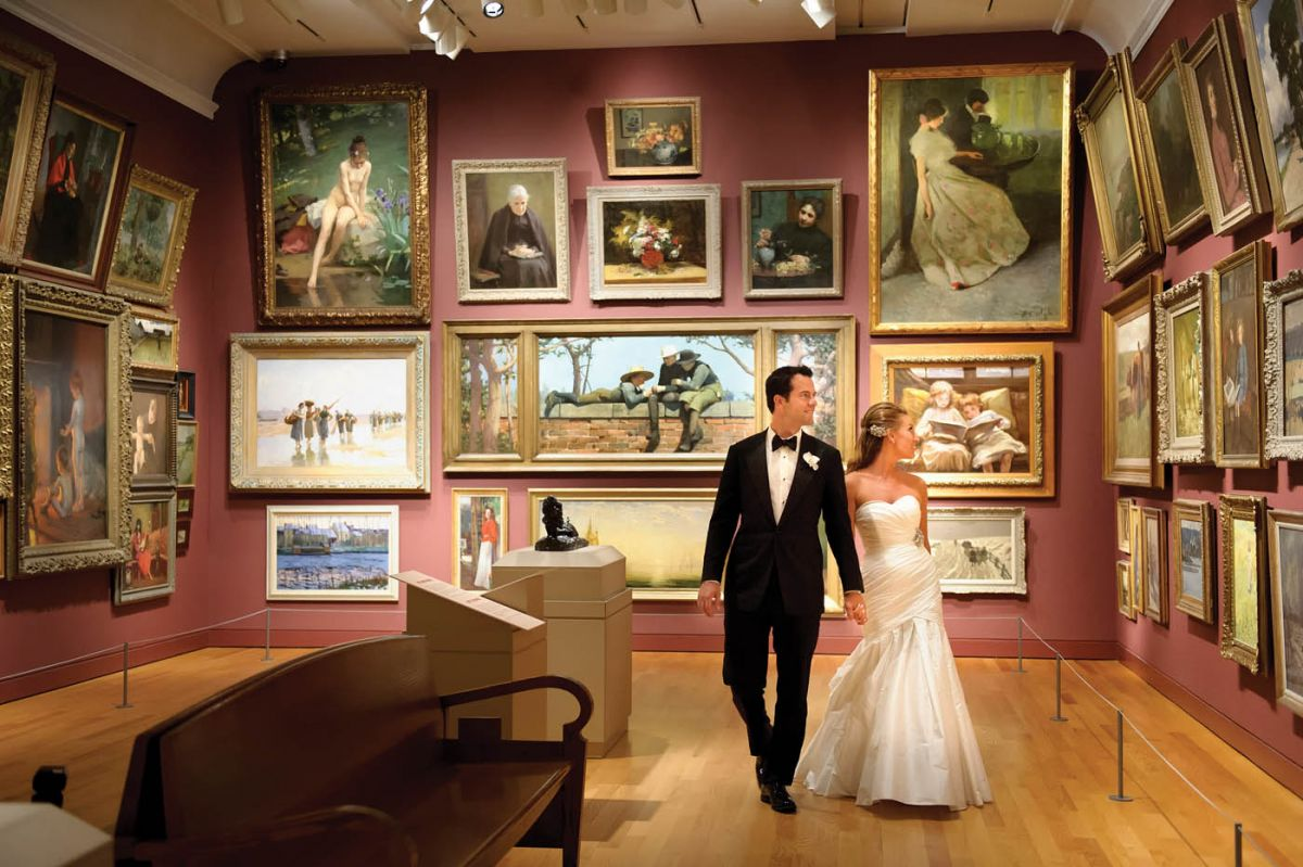 bride and groom holding hands and looking at paintings in gallery