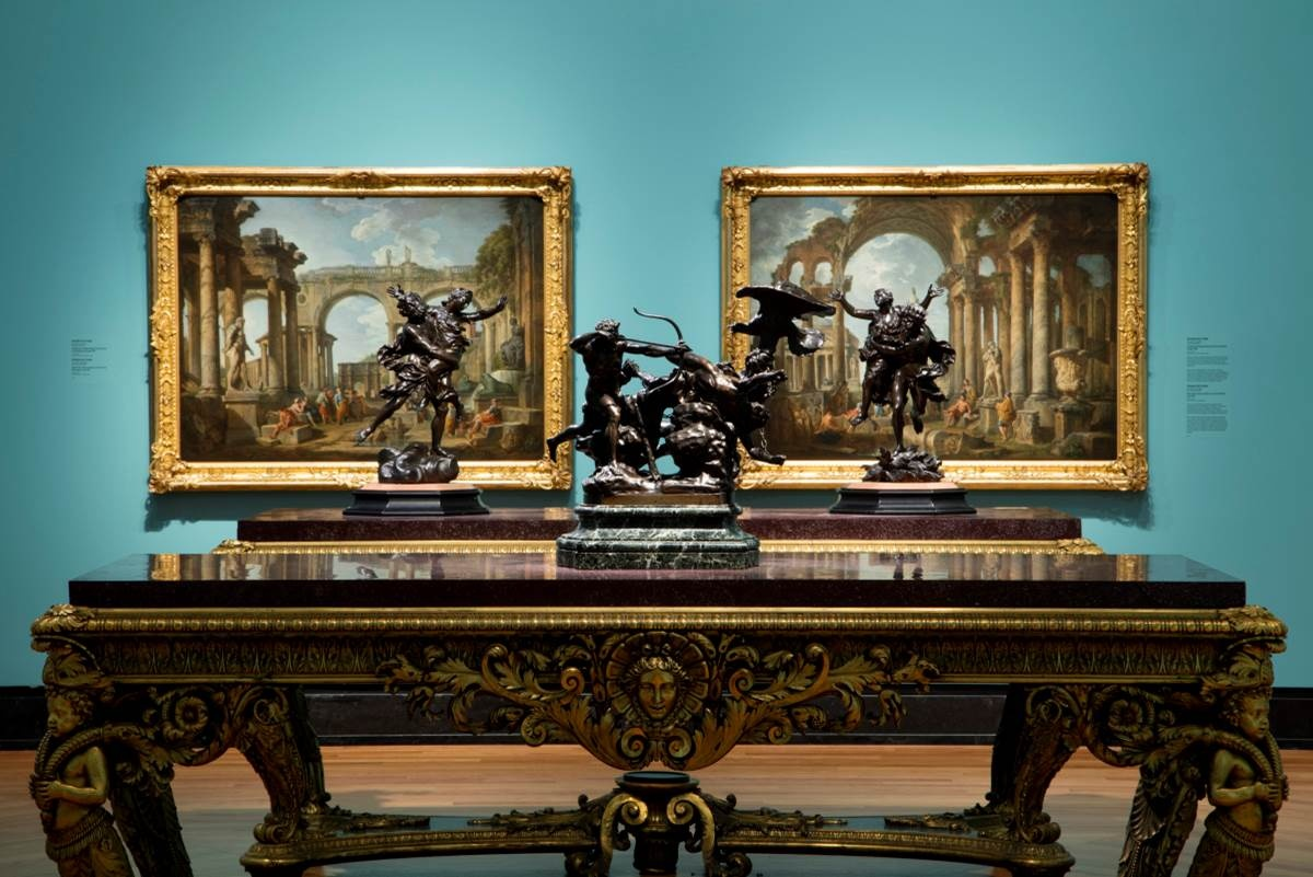 Ornate table with statues on top and paintings hanging behind